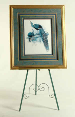 Metal easel with tall framed art print with peacock