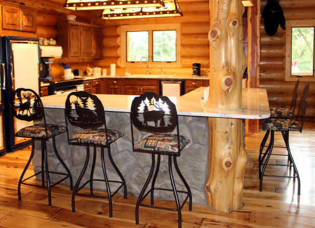 Residential home with rustic lodge swivel bar stools seated around a very rustic designed kitchen